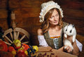 Peasant woman holding a rabbit table with vegetables and fruit stands next to a Royalty Free Stock Images