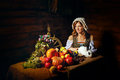 Peasant woman holding a rabbit table with vegetables and fruit stands next to a Royalty Free Stock Photography
