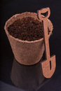 Peat pot with nutrient soil and decorative wooden shovel on a black background Stock Photography