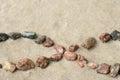 Pebble infinity symbol on sand selective focus