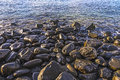 Pebble stone beach in morning light with harmonic reflections Royalty Free Stock Images
