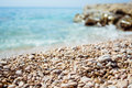 Pebbles beach with perfect turquoise sea in background Royalty Free Stock Images