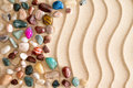 Pebbles and gemstones on golden beach sand arrangement of waterworn colorful tumbled polished with an undulating wavy pattern Stock Images