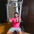 Pec deck flye pec deck chest workout man fly flies exercise at gym Stock Image