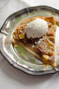 Pecan apple pie with ice cream a piece of and a scoop of on a rustic platter Royalty Free Stock Photo