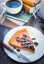 Pecan cake and pumpkin on plate with tea and books on wooden background toned picture Stock Photo