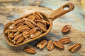 Pecan nuts in a rustic scoop against a grunge wood background Royalty Free Stock Photography