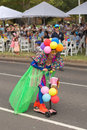 Peculiar women at moomba parade a wearing balloon arrangement on her head and colourful accessories driving scooter Royalty Free Stock Image