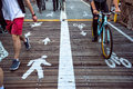 Pedestrian and bicycle riders sharing the street lanes with road marking in the city. Royalty Free Stock Photo