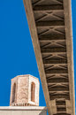 Pedestrian bridge viewed from below against blue sky the bottom of a concrete with an old stone watch tower to the left all set a Stock Photo