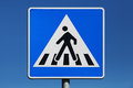 Pedestrian crossing road sign above blue sky background Stock Photo