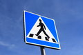 Pedestrian crossing sign on blue sky background Stock Photo