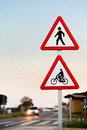Pedestrian and cycling crossing sign with car lights in background selective focus Stock Photos