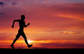 Pedestrianism silhouette of sportsman silhouette of running on man sunset fiery background Royalty Free Stock Image