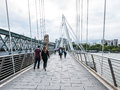 Pedestrians cross jubilee bridge over thames river london august the Stock Image