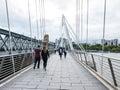 Pedestrians cross jubilee bridge over thames river london august the Stock Image