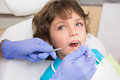 Pediatric dentist examining a little boys teeth in the dentists chair Royalty Free Stock Photo