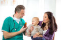 Pediatric doctor giving pills bottle to mother with baby Stock Photos