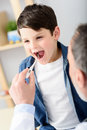 Pediatrician checking temperature of sick patient Royalty Free Stock Photo