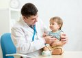 Pediatrician examining heartbeat of baby with Royalty Free Stock Photo