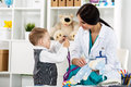 Pediatrician with patient family doctor examination little child visiting playing stethoscope beautiful female medical freckled Stock Photography