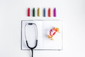 Pediatrics equipment with crayons, copybook white background top view space for text Royalty Free Stock Photo