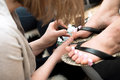 Pedicure nail polish a pedicurist paints the toes of her client Stock Images
