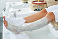 Pedicure nourishing mask legs cling film wrap moisturizer heat effect in nail salon Royalty Free Stock Photography