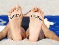 Pedicure woman s feet and toes with smiley faces on a beach Stock Photo