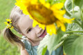 Peek a boo girl hides behind sunflower and peeks out Stock Images