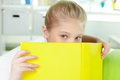 Peeking out of book portrait lovely girl yellow Royalty Free Stock Photo