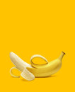 Peeled banana on yellow background with copyspace Stock Images