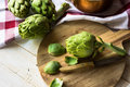 Peeling fresh ripe artichokes, preparing for cooking, round wood cutting board, knife, kitchen linen towel, copper dipper Royalty Free Stock Photo