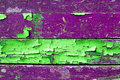 Peeling paint on old weathered wood with peeling paint of green and violet colors- textured wooden background Royalty Free Stock Photo