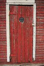 Peep hole in old red door weathered exterior shed Stock Photography