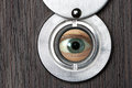 Peephole with eye horizontally close up on a wooden door Royalty Free Stock Image