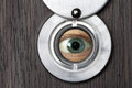 Peephole with eye horizontally close up on a wooden door blurred foreground Royalty Free Stock Photography