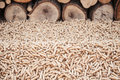 Pellets biomas pine infront a wall of firewoods Stock Images