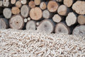 Pellets biomass pine infront apile of fire wood Royalty Free Stock Photos