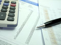 Pen on financial documents with calculator black and figures Stock Photography