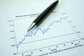 Pen and graph on financial graph black lying Stock Image