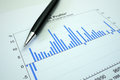Pen and graph on financial profit graph black lying bar showing Royalty Free Stock Image