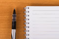 Pen and notebook close up view of black white blank on wood background Royalty Free Stock Images
