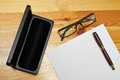 Pen paper pen holster and glasses on a wooden table Royalty Free Stock Images