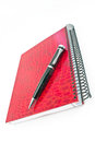 Pen on red spiral notebook isolated white Stock Photography