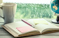 Pen and sticky note on open notebook on coffee cup and globe Royalty Free Stock Photo