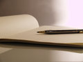 Pen to lined paper note book and on a desk ready write thoughts Stock Photos