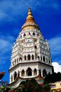 Penang malaysia kek lok si temple pagoda seven story with painted figures of buddha set in its niches topped by a gold spire at Royalty Free Stock Photo