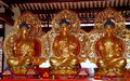 Penang malaysia three gilded buddhas at chinese temple seated inside a prayer pavilion the taoist tien gong tan Royalty Free Stock Photography