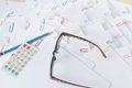 Pencil and calculator with spectacles on stack of overload paper Royalty Free Stock Photo